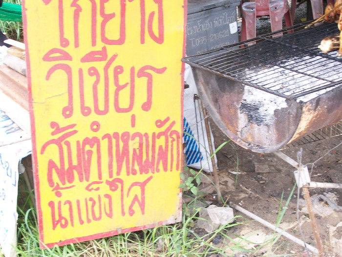 Thai sign next to a street food stall